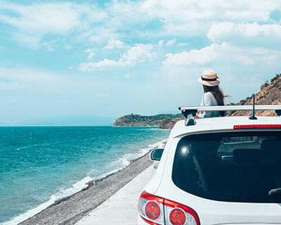 woman standing next to car on road trip