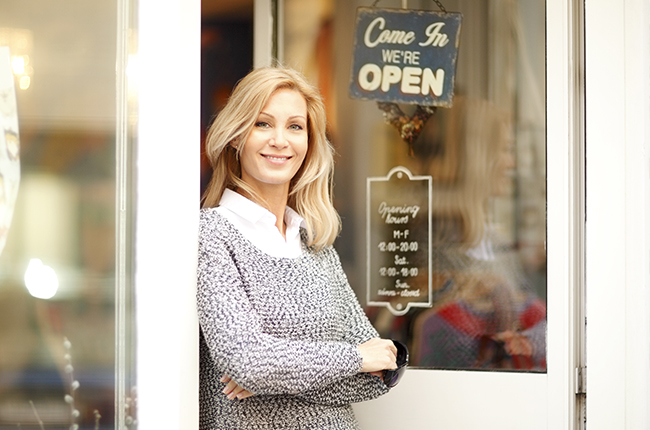 woman standing in front of her small business