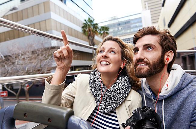 Couple riding a tour bus through city